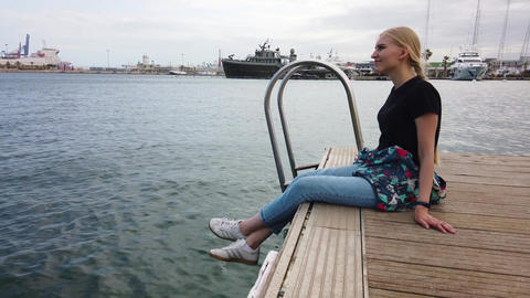 Girl sitting alone on edge of pier bank in port in front of parked sailboats and Live Action