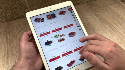 A man orders berries in an online store using a tablet. The choice of products Live Action
