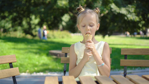 Little girl eating ice-cream outdoors at summer in outdoor cafe Live Action