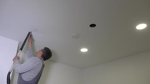 builder man saw round hole in plasterboard ceiling Live Action
