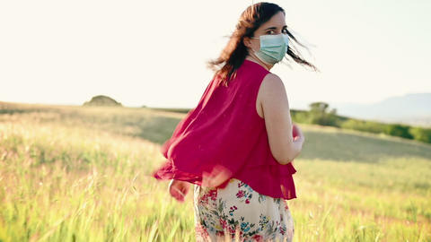 Woman throwing away her protective face mask. Happy young woman running free in Live Action