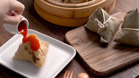 Eating rice dumpling zongzi - Young girl is eating fresh Chinese food at home on dark wooden table Live Action