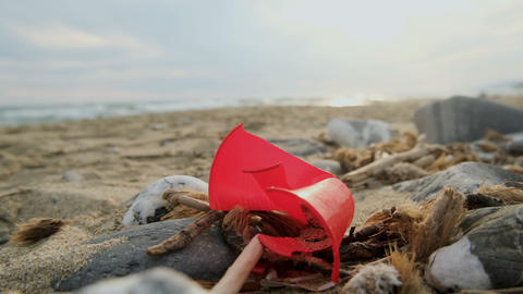 Red disposable plastic glass discarded on sandy sea shore ecosystem,pollution Live Action