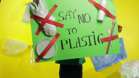 Girl activist holding green poster Say no to Plastic. Plastic nature pollution Live Action