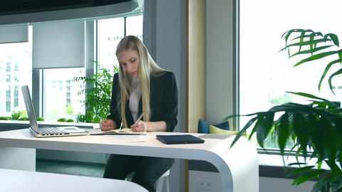 Elegant woman working in stylish office. Modern blond woman in trendy suit Live Action