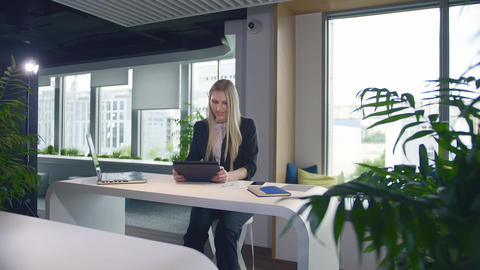 Stylish business woman with tablet in office. Elegant woman in suit sitting at Live Action