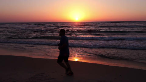Silhouette of a man running along the seashore in the evening Footage