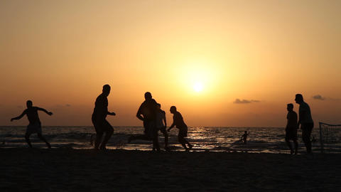 Silhouettes of football teams in the beach at sunset at the sea ビデオ
