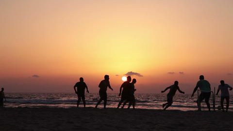 Football on the beach at sunset Footage