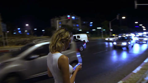 Attractive girl walking down the street and use the smartphone in the evening Footage
