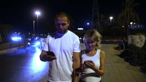 Young couple going through the evening the city and using smart phones Footage