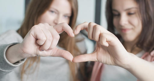 Close-up of two female hands making heart shape. Focus changes to beautiful Live Action