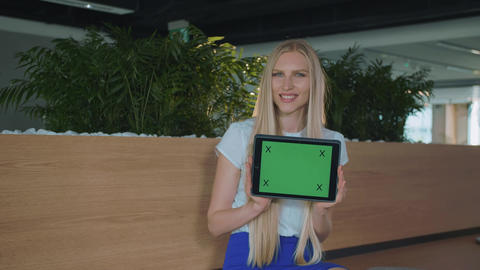 Woman showing tablet in office. Young smiling blond woman showing tablet with Live Action
