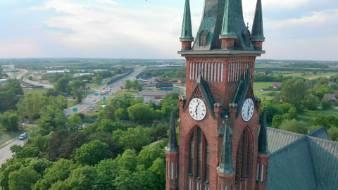 Church in small city among pastures. Drone footage. Red Church is Roman Catholic Live Action