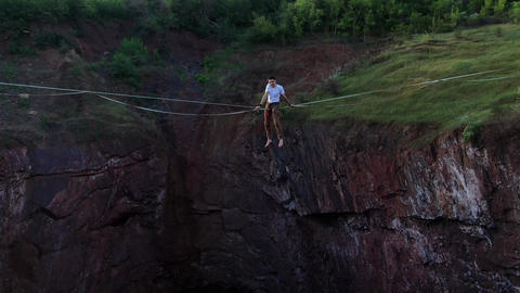 A man is sitting on a slackline over a natural pit, aerial view, nature, 4k Live Action