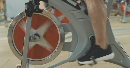 Side view of male feet in sneakers pedaling cycling equipment in sports club Live Action