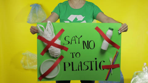 Unrecognizable woman holding protesting poster Say No To Plastic. Environment Live Action