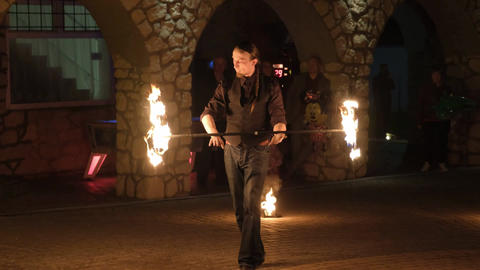 Man is rotating the fire staff. Dangerous magic tricks with fire Live Action