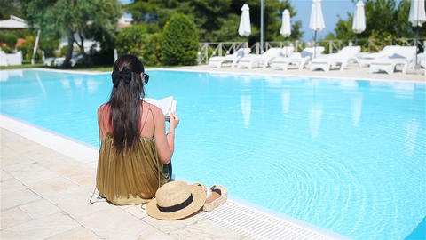 Woman relaxing by the pool in a luxury hotel resort enjoying perfect beach Live Action