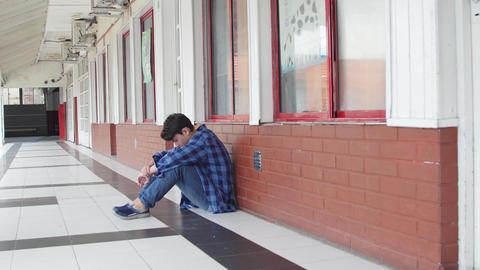 Caucasian boy bullied at school; seated on school hallway. Slow motion Live Action