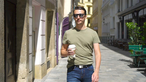 Happy young urban man drinking coffee in european city outdoors Live Action