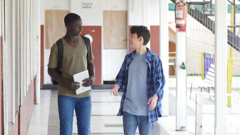 Slow motion of african and caucasian teenagers talking in school hallway Live Action