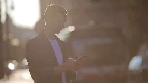 Young man using cellphone outdoors on the street in soft light Live Action