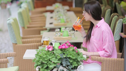 Portrait of young beautiful woman sitting in a cafe outdoor drinking tasty Live Action