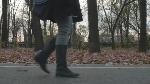 4k - Young beautiful woman in long boots taking a walk on an alley in the park Footage
