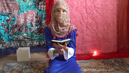 Girl In Yashmak Sitting On A Rug And Reading A Book Footage