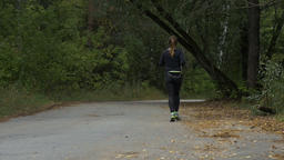 young woman running on road in autumn woods Footage
