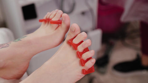 Pedicure master treats toes to a woman Live Action