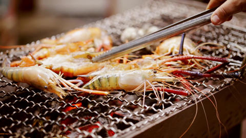 Grill shrimp , barbecue seafood on fire puts the shrimp on grill. Grilled seafood on bbq. Cooking Live Action