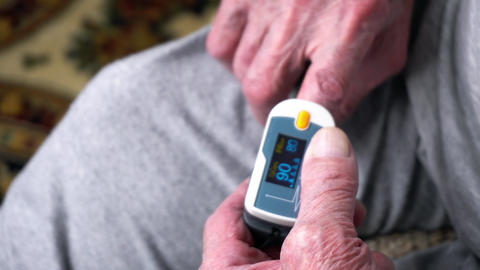 Old man is using pulse oximeter at his finger to measure his pulse Live Action