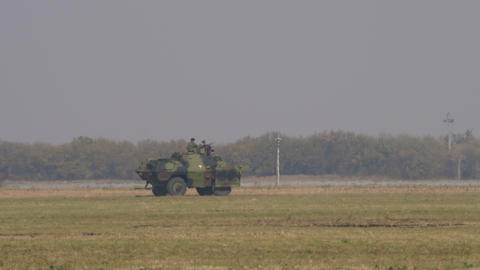 Green Mimecic Camouflage Military Vehicle Run at Fast Speed on the Battlefield Live Action