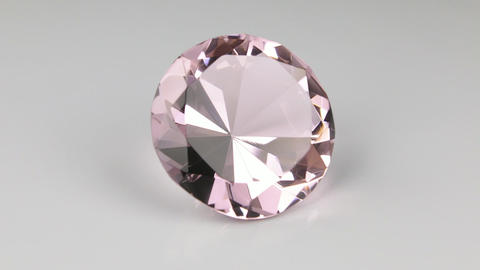 Rotation of a large pink rhinestone on a white background Live Action