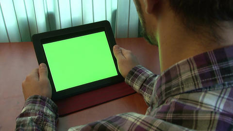 Man using digital tablet with a green screen to add your own custom content (and Footage