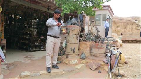 Bedouin kindles coals for hookah outside a souvenir shop Footage