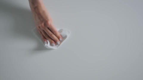 Slow motion: woman cleaning white table with wet wipe - close up top view Live Action