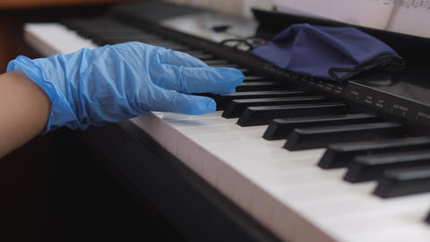 Electronic piano. Fingers press the piano keys. Hands in rubber gloves. Pandemic 2020, Live Action