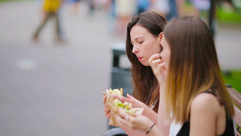 Caucasian women eats hamburger fast food sandwich on the street outdoors. Active Live Action