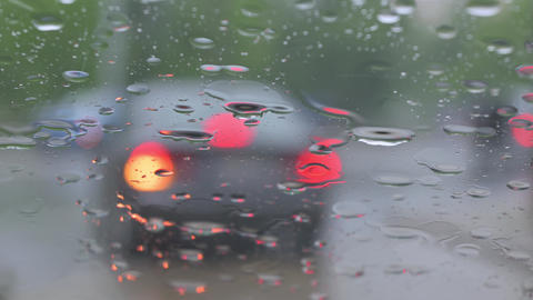 Rain drops falling on car windshield, blurred traffic outside Live Action