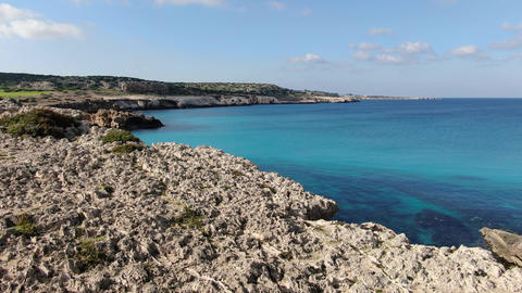 Aerial view of crystal clear blue lagoon with rocky coast around. Drone view of Live Action