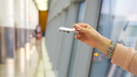 Female hand holding toy airplane, copy space for text. Passenger with small Live Action