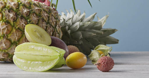 Freshly picked natural ripe exotic fruits with ripe pineapple on a wooden gray Live Action