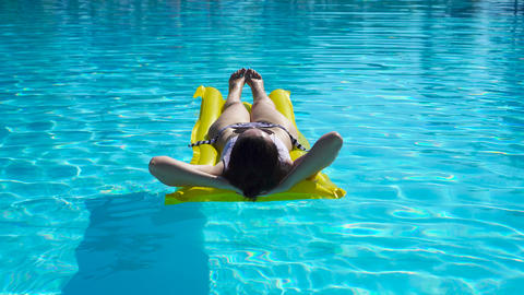 Young woman relaxing with air mattress in outdoors swimming pool Live Action