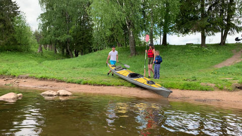 Russia, Gatchina, 07 June 2020: Couple lowers a kayak on water of the river in Acción en vivo