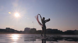 Girl silhouette dancing on beach with fabric fluttering on the wind against sun Footage