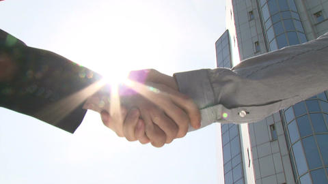 Two businessmen shaking hands in front of office building Footage