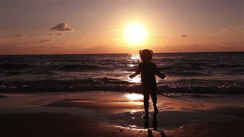 Little girl jumping on the beach at sunset Footage